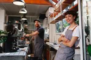 happy woman baristas working in modern cafe kitchen