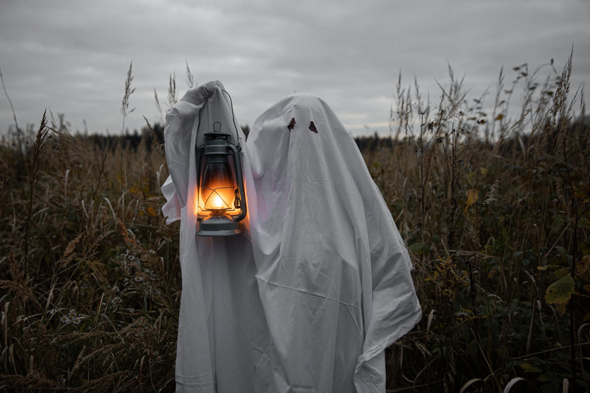 personin ghost costume holding a lantern